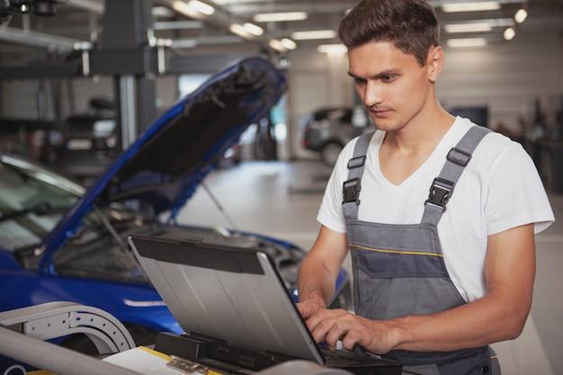 彼のガレージで若いハンサムな自動車修理工車両