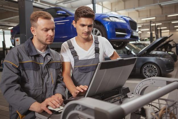 Два мужских механика работают в гараже