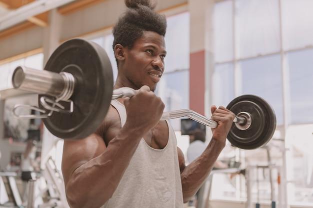 バーベルでワークアウト若いスポーツマン