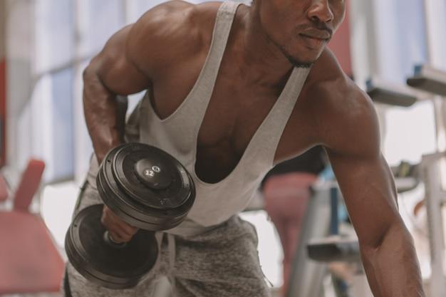 Спортивная (ый) африканский мужчина работает с гантелями в тренажерном зале