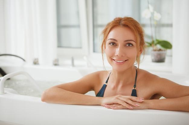 スパセンターでハイドロマッサージ浴槽で美しい女性