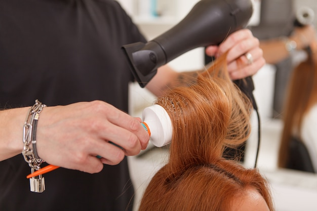 女性のクライアントの髪をスタイリングする美容師