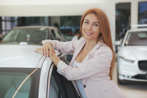 ディーラーで新しい車を選ぶ豪華な女性
