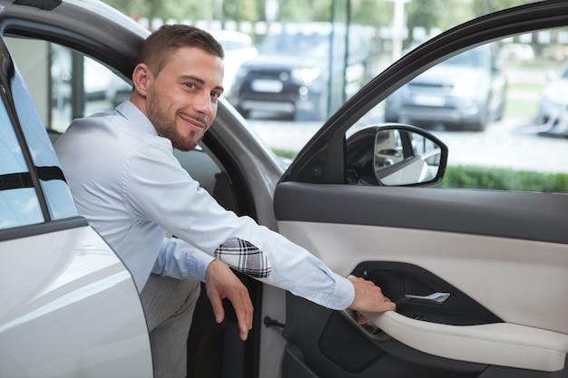 Красивый молодой человек, покупая новый автомобиль в автосалоне