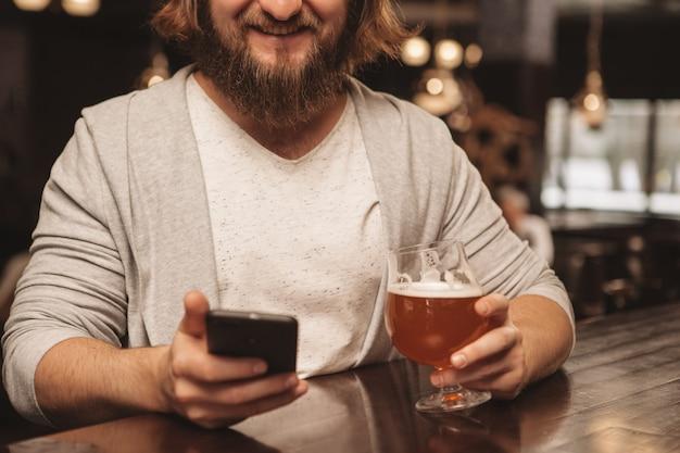 パブでビールを飲んで楽しんでいるひげを生やした若い男