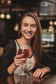地元のパブでビールを飲んで楽しんでいる美しい女性