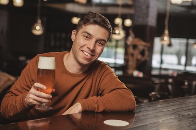 Красивый молодой человек пьет пиво в баре