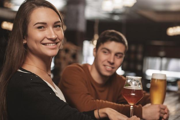 バーでデートにビールを飲んで幸せな若いカップル