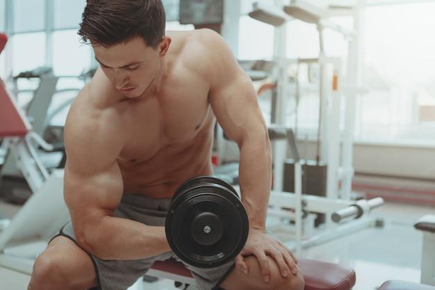 Разорванный без рубашки мужчина упражняется с гантелями в тренажерном зале