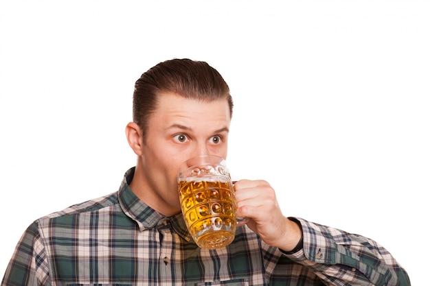 若い男が白で隔離のビールを飲みます。