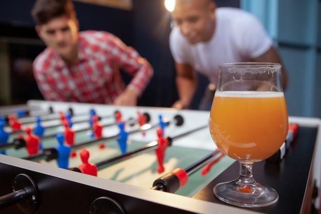 ビールパブでテーブルサッカーをしている友人のグループ