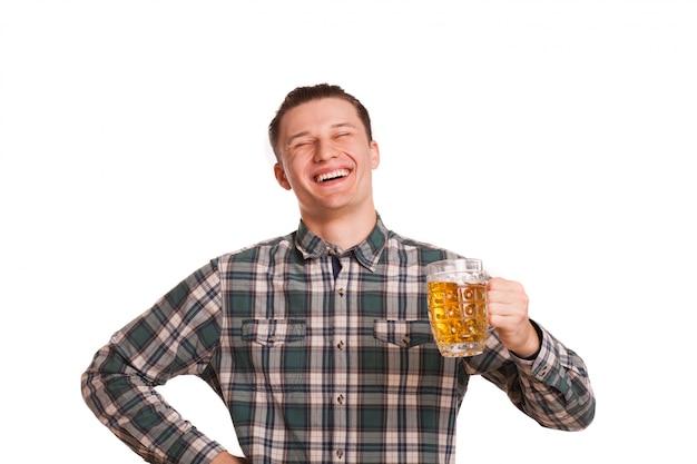 Молодой красивый счастливый человек, радостно смеясь, держа бокал пива, изолированные на белом. привлекательный мужчина улыбается, выглядит возбужденным, позирует с бокалом пива, копией пространства