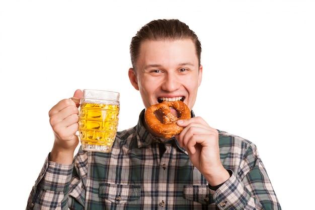 オクトーバーフェストを祝うビールのグラスを保持しているプレッツェルを食べて楽しんでいる陽気な若い男。ビールを飲むと白で隔離される軽食を食べて幸せなハンサムな男