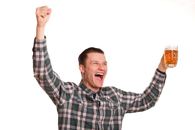 Молодой красавец кричал с пивом в руке, смотреть футбол и праздновать победу своей любимой команды. выразительный мужчина держит бокал пива, кричит