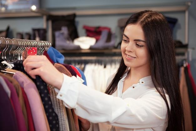 素敵な若い女性が衣料品店で買い物