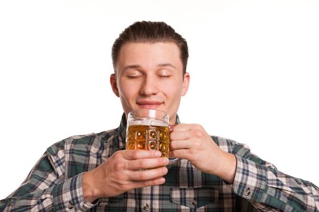 白で隔離おいしいビールの臭いがして、目を閉じて笑顔でハンサムな男は喜びで閉じた。オクトーバーフェストを祝ううれしそうな男。レストラン、バー、パブのコンセプト