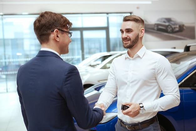 ハンサムな男がディーラーで新しい車を買う