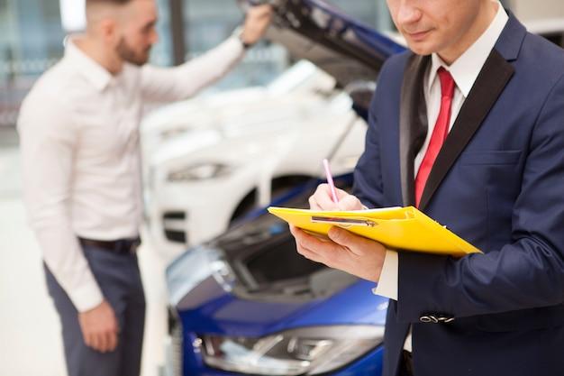 Неузнаваемый мужчина покупает новую машину в автосалоне