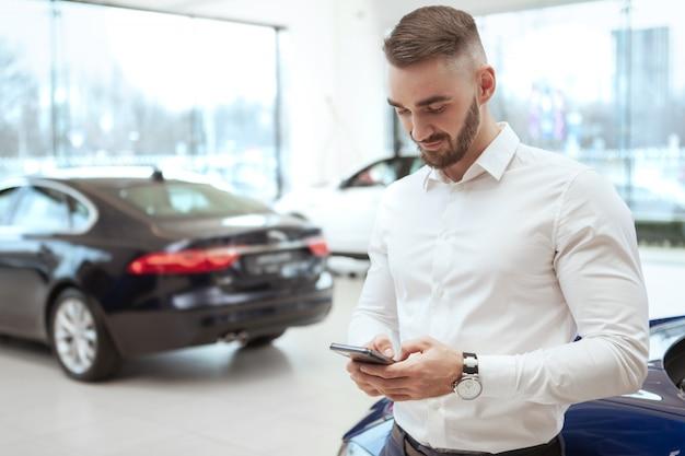 Красивый мужчина выбирает новый автомобиль в автосалоне