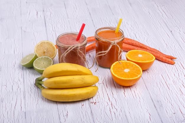 赤とオレンジのデトックスコククテルは、果物と白のテーブルに立つ