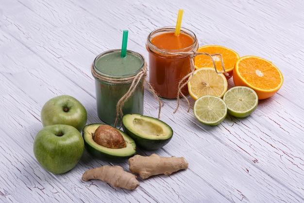 緑色とオレンジ色のデトックス・コクツールは、白と野菜の白いテーブルの上に立つ