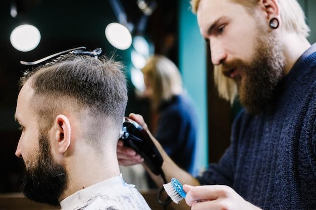 ブロンドのひげ剃りのバーダーは、人の髪を注意深く褪せさせる