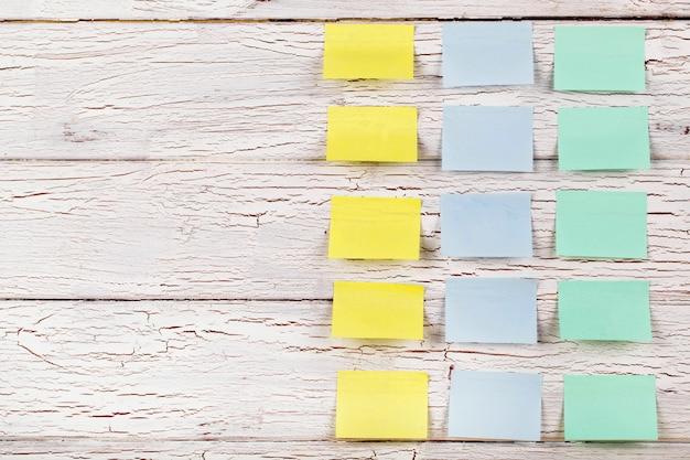 黄色、青、緑のステッカーは、白い木製の床に固定されています