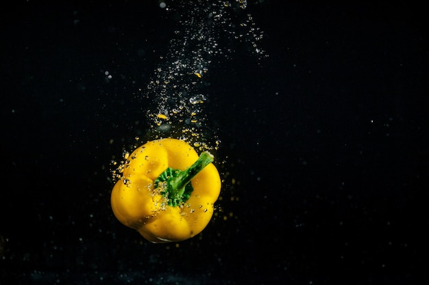 泡が水の中に落ちる黄色の胡椒の周り