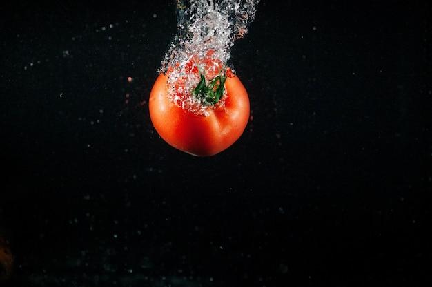 新鮮な大きなトマトは水に落ちて泡を作ります