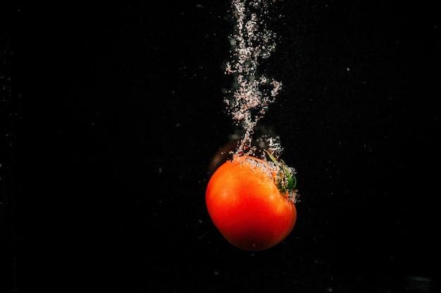 鮮やかな赤いトマトは水の中に落ちて、それを飛ばします
