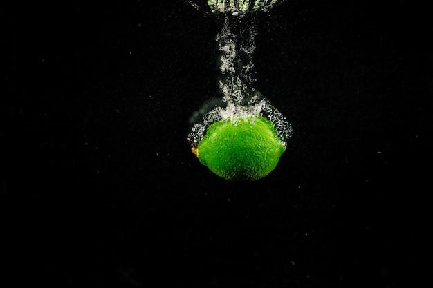 緑色の石灰が黒い背景に水を注ぐ
