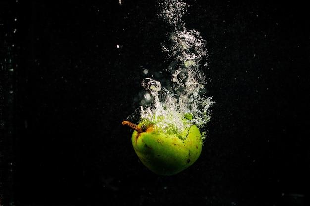 緑色の梨が黒い背景に落ちてくる水