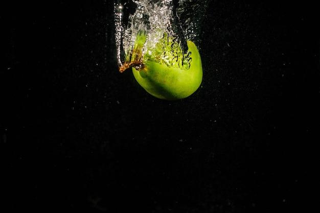 緑の梨は、黒の背景に水に落ちる