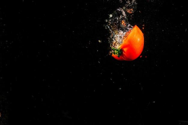 トマトの半分が黒の背景に落ちる