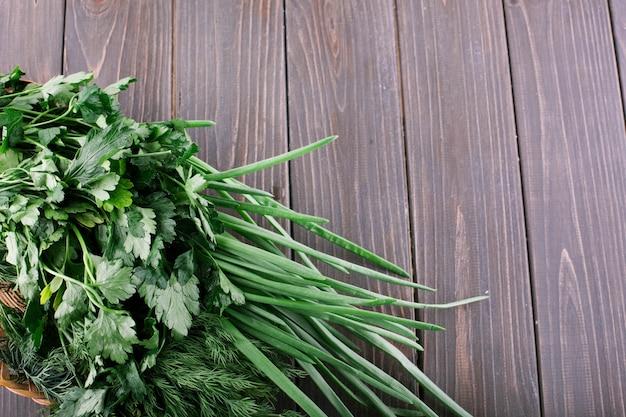 Куча зеленого лука, петрушки и дыни лежат на маленькой корзинке на темном деревянном столе