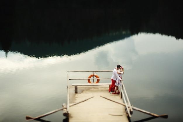 男と女は山の湖の上の木製のポーチに立つキス