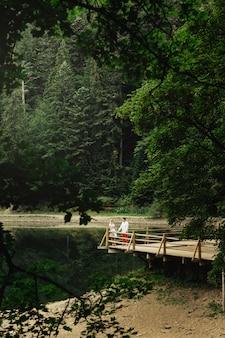 山の湖の上の木製のポーチに立っている素敵なカップルを遠くから見る