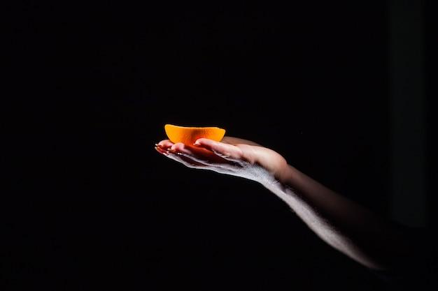 女はオレンジの半分彼女の手に保持