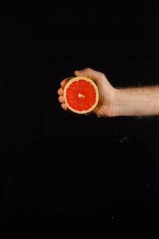 黒の背景に人間の手でジューシーなグレープフルーツの半分