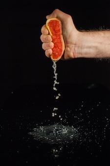 人の手で保持されている果物の半分からグレープフルーツジュースが飛び散る