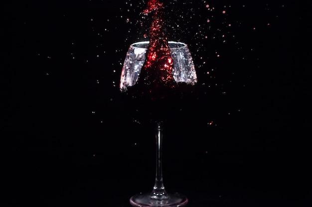 Красный сок брызгает в хрустальном стекле, стоящем в черном пространстве