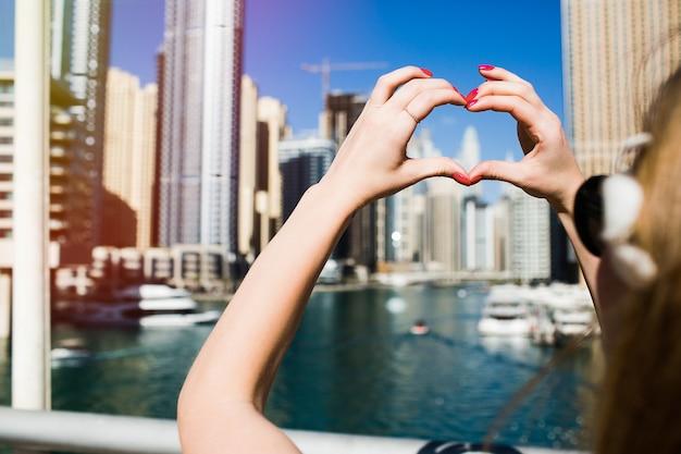 赤い爪の女性はドバイの高層ビルの前に彼女の指で心を示します