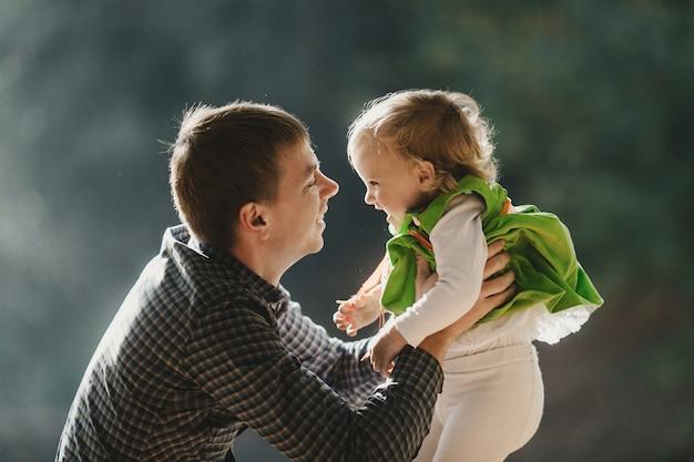 Отец держит в руках свою дочь