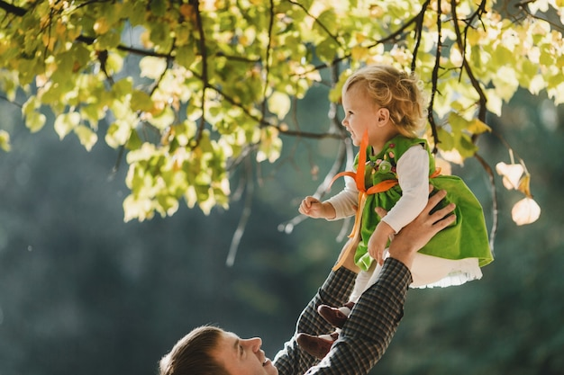 Отец держит в руках свою дочь в парке