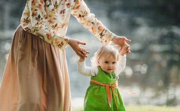 Мать с дочерью гуляют около озера