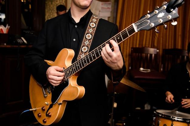 黒いシャツの男はギターで演奏する
