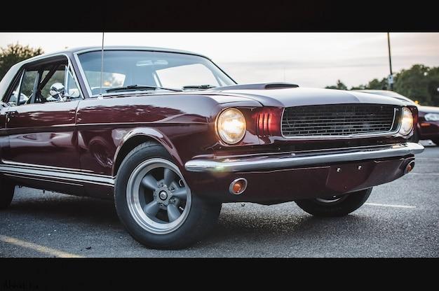 古い赤いアメリカの車は、夕方に通りに立っています