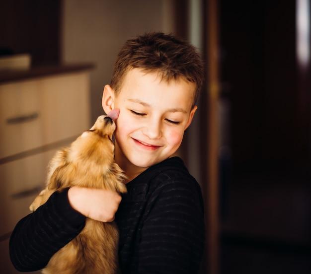 かわいい子は小さな犬を抱擁する