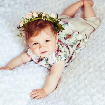 Девушка в цветочном венке смотрит вверх, отдыхая на пушистом одеяле
