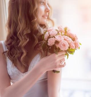 花嫁は窓の上に座って彼女の肩の前に少しピンクの花束を保持しています